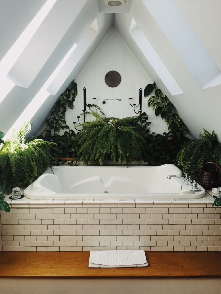 White hot tub with cream metro tiling in alcove surrounded by bathroom plants