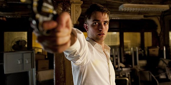 Robert Pattinson aiming a gun in Cosmopolis