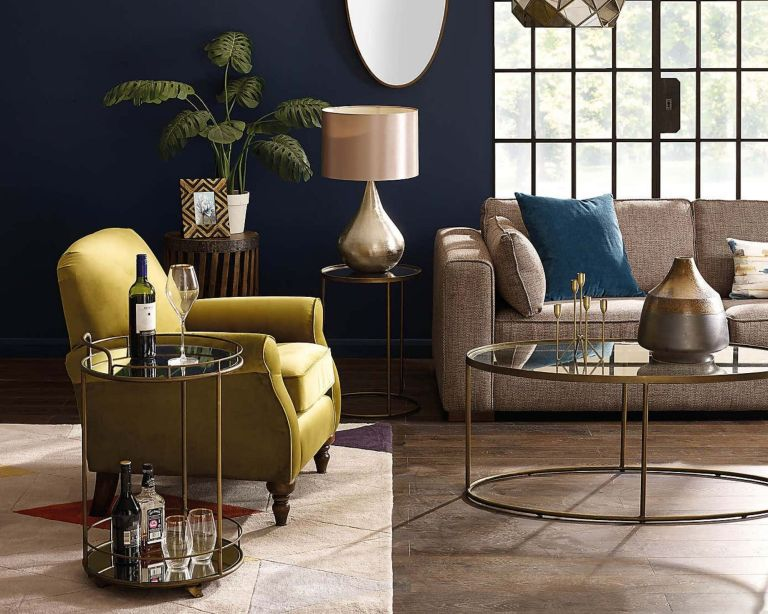 Antique Brass Drinks Trolley in dark living room beside armchair, with crittall-style doors, beige sofa and wooden floors