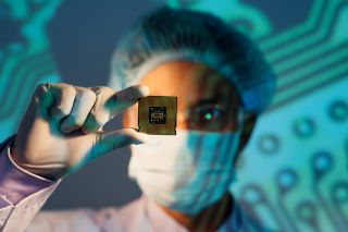 Stock image of engineer holding chip