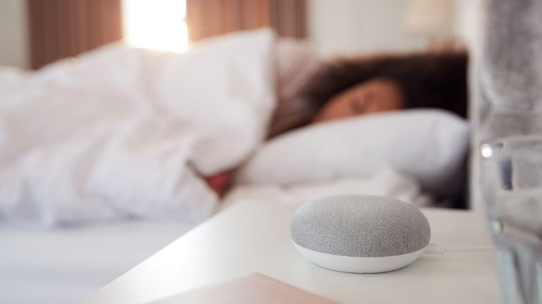 woman in bed using white noise for sleep, machine in foreground