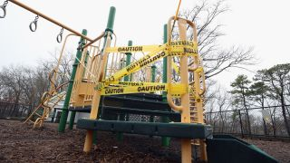 Access to children's playground equipment is taped off on March 30, 2020 in Oyster Bay on Long Island, New York, amid the coronavirus pandemic..