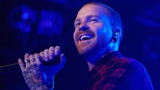 A close-up of Matty Mullins smiling onstage