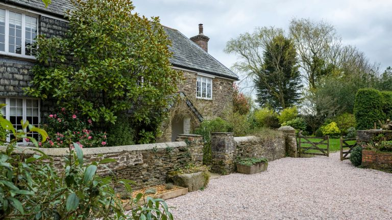 An example of front garden ideas showing a country house with a gravel drive, a stone wall and a traditional front garden