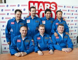 "The six-man crew of the Mars500 mission is getting set to ""land"" on the Red Planet next month. (Seven crewmembers are shown here; one serves as a backup for those inside the mock capsule.)"