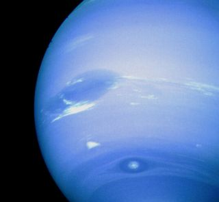 Neptune's Great Dark Spot, accompanied by white high-altitude clouds, as seen by a Voyager spacecraft.
