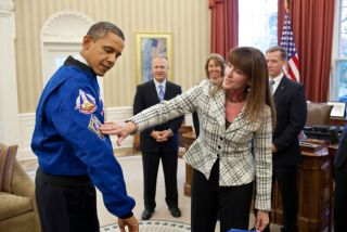 Janet Kavandi, Director of Flight Crew Operations at Johnson Space Center, presents President Obama with a jacket during a drop by with the crew of the Space Shuttle Atlantis in the Oval Office, Nov. 1, 2011. The jacket features patches from several past