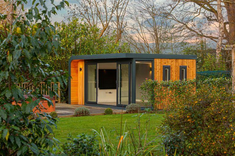 Modern garden office clad in warm wood in a large garden
