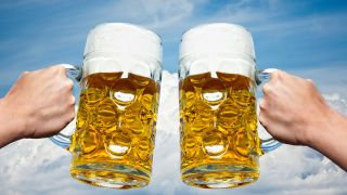 Two Full Beer Steins Clinking Together Against A Bright Blue Sky Backdrop