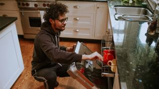 How to install a dishwasher yourself: Man loading dishwasher