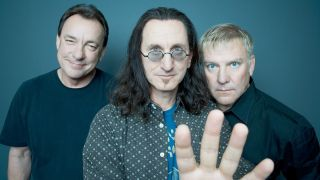 Rush singer and bassist Geddy Lee raises his hand as bandmates Neil Peart and Alex Lifeson stand behind him