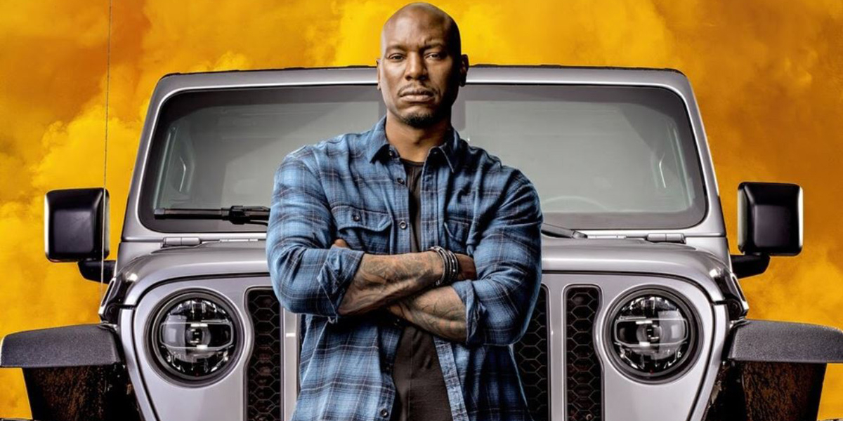 F9 Tyrese Gibson poses in front of a Jeep and some fire