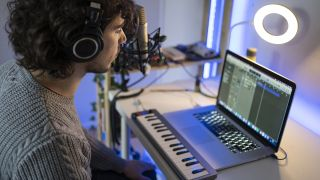 Man creates music with a laptop and keyboard