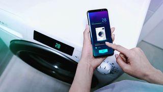 Someone using a smart washing machine via their smartphone