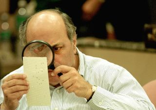 Punch cards have their issues. Here, Judge Robert Rosenberg of the Broward County Canvassing Board examines a dimpled chad on a punch-card ballot Nov. 24, 2000, during a vote recount in Fort Lauderdale, Florida.