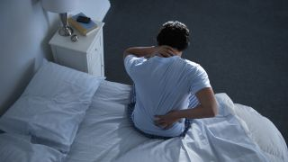 A man sits up in bed at night, holding one hand to his lower back because he's experiencing back pain