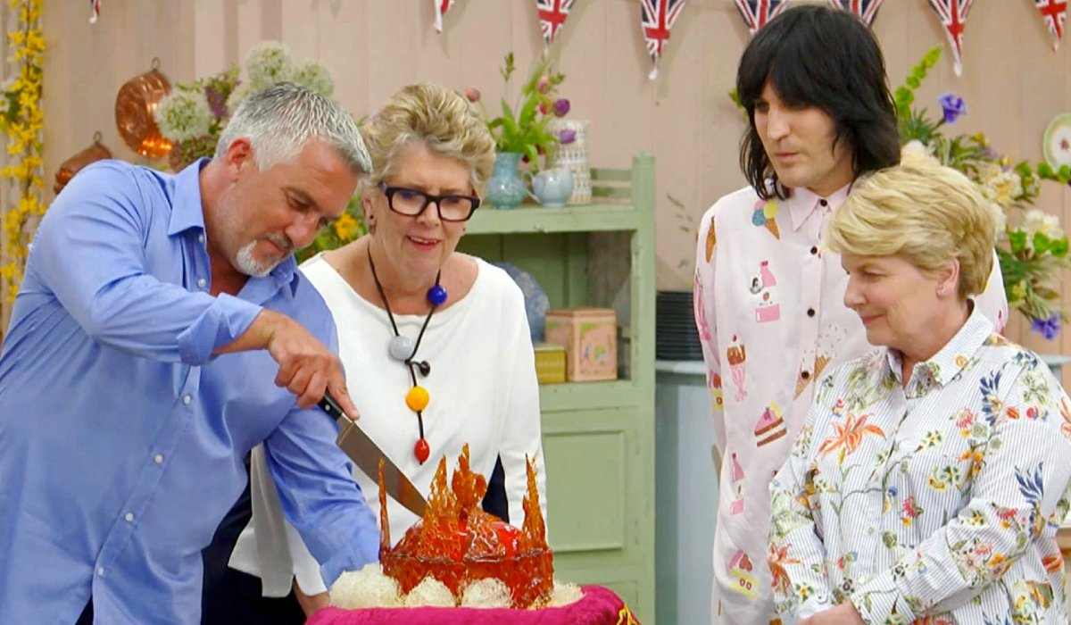 Great British Baking Show Paul cuts a cake while Prue, Sandi, and Noel watch