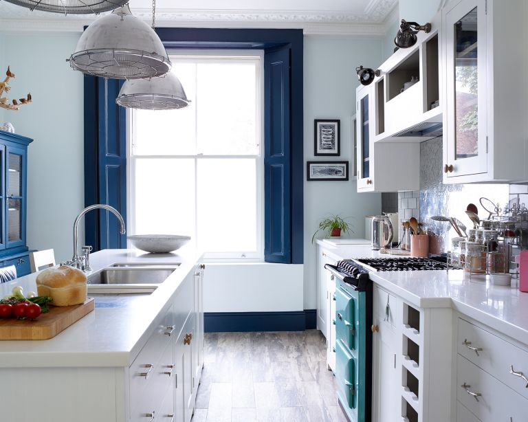 An example of kitchen cabinet ideas showing a white and blue kitchen with a narrow island and large window