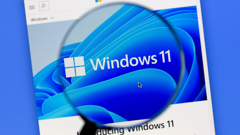 The Windows 11 logo seen through a digital magnifying glass