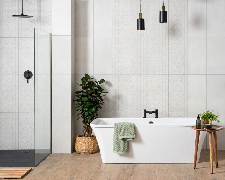 White bathroom ideas: Freestanding white bath with white tiled wall, shower unit and indoor houseplant on wooden flooring