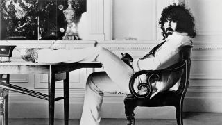 A photograph of Vangelis looking cool with his foot up on the table