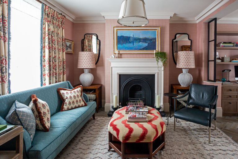 A small living room with pink walls, blue sofa and red and white patterned ottoman, drapes and cushions.
