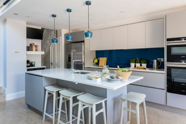 modern kitchen diner with a large white kitchen island, blue feature splash back and blue pendant lights