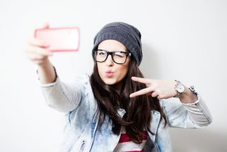 Pretty hipster girl taking selfie and making duck face. Sending kisses and holding peace sign.