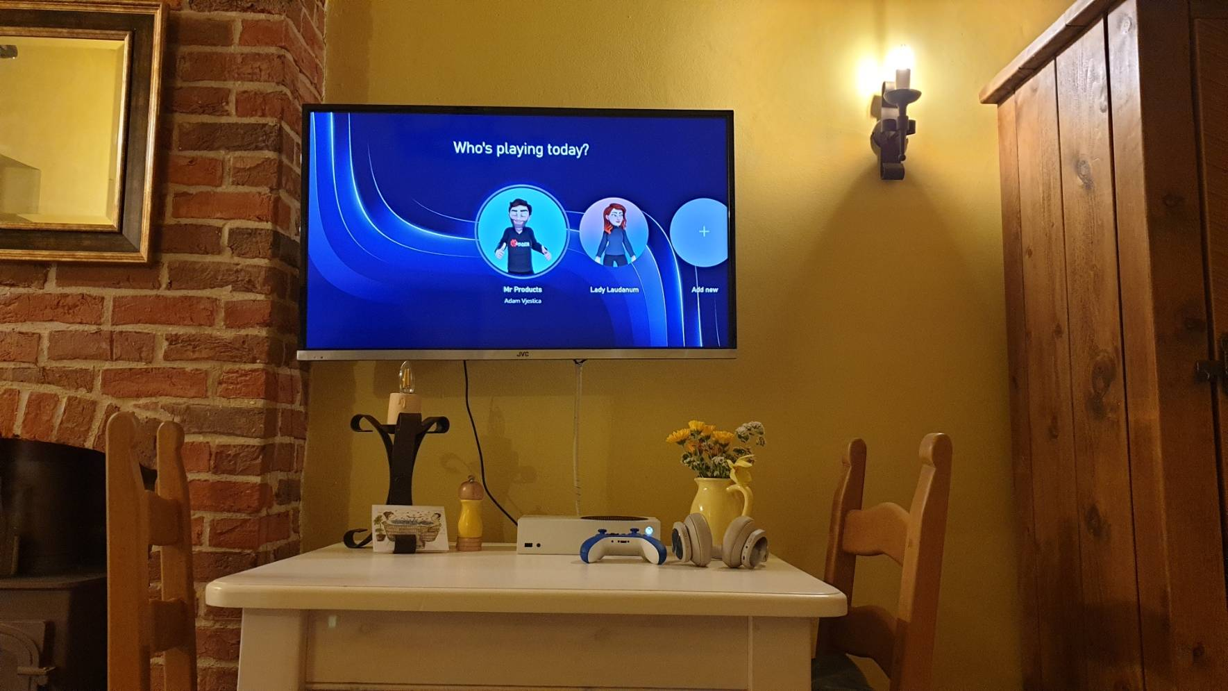 Wall mounted TV showing Xbox sign in screen and Xbox Series S console on table in a cottage