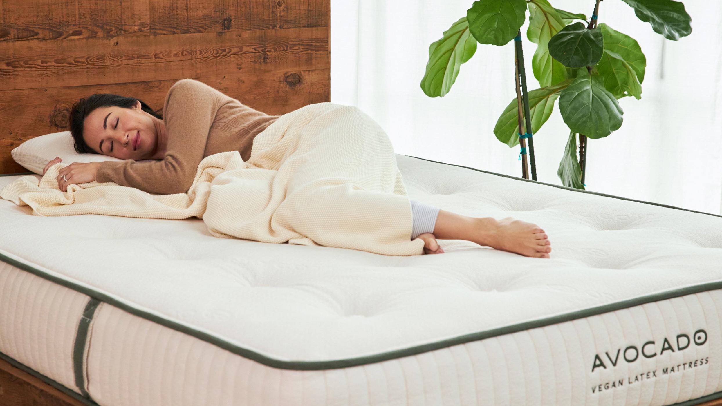 Saatva vs Avocado: A woman with brown hair sleeps on top of the Avocado Vegan Latex Mattress