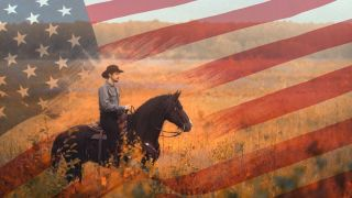 cowboy on horse in front of American flag