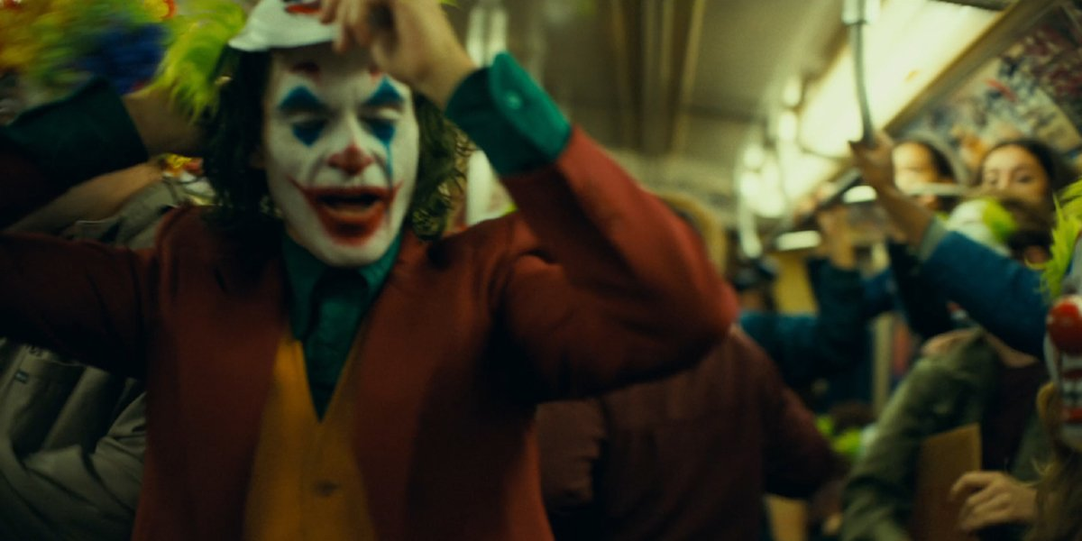 Joker puts on a clown mask in the subway