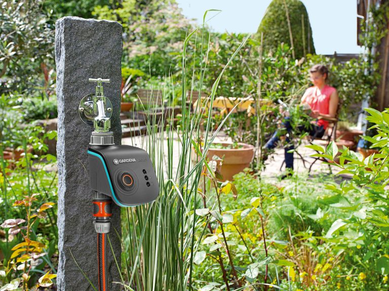best self watering gadgets and accessories, garden and greenery with a smart irrigation system connected to an outdoor water tap and a woman sitting in the background