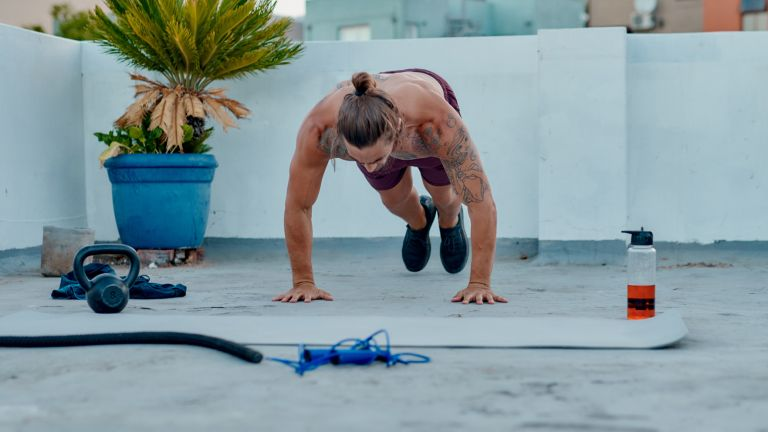 Man doing burpees on a rooftop