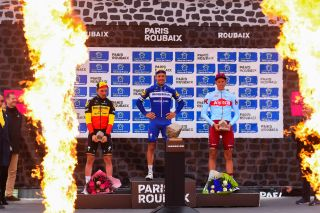 The Paris-Roubaix podium, flanked by pyrotechnics