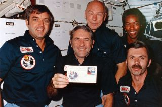 Space shuttle Challenger commander Richard Truly, floating in the orbiter's middeck, holds up one of the 10 envelopes, or covers, that he and his four STS-8 crewmates autographed while in orbit. Truly, a stamp collector, is finally receiving one of the collectibles after 38 years thanks to a fellow philatelist, David Ball.