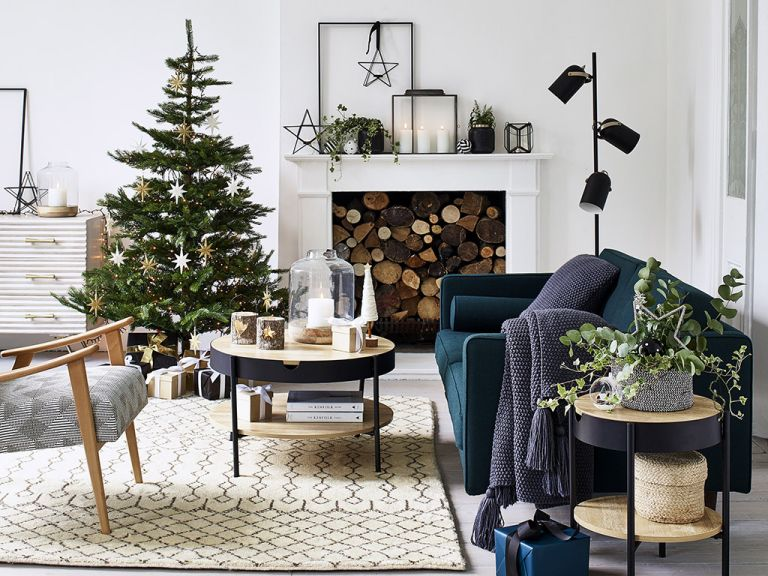 White living room with a feature fireplace decorated for Christmas