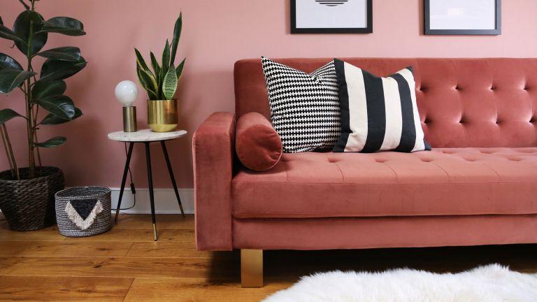 pink velvet sofa with black and white striped throw pillows
