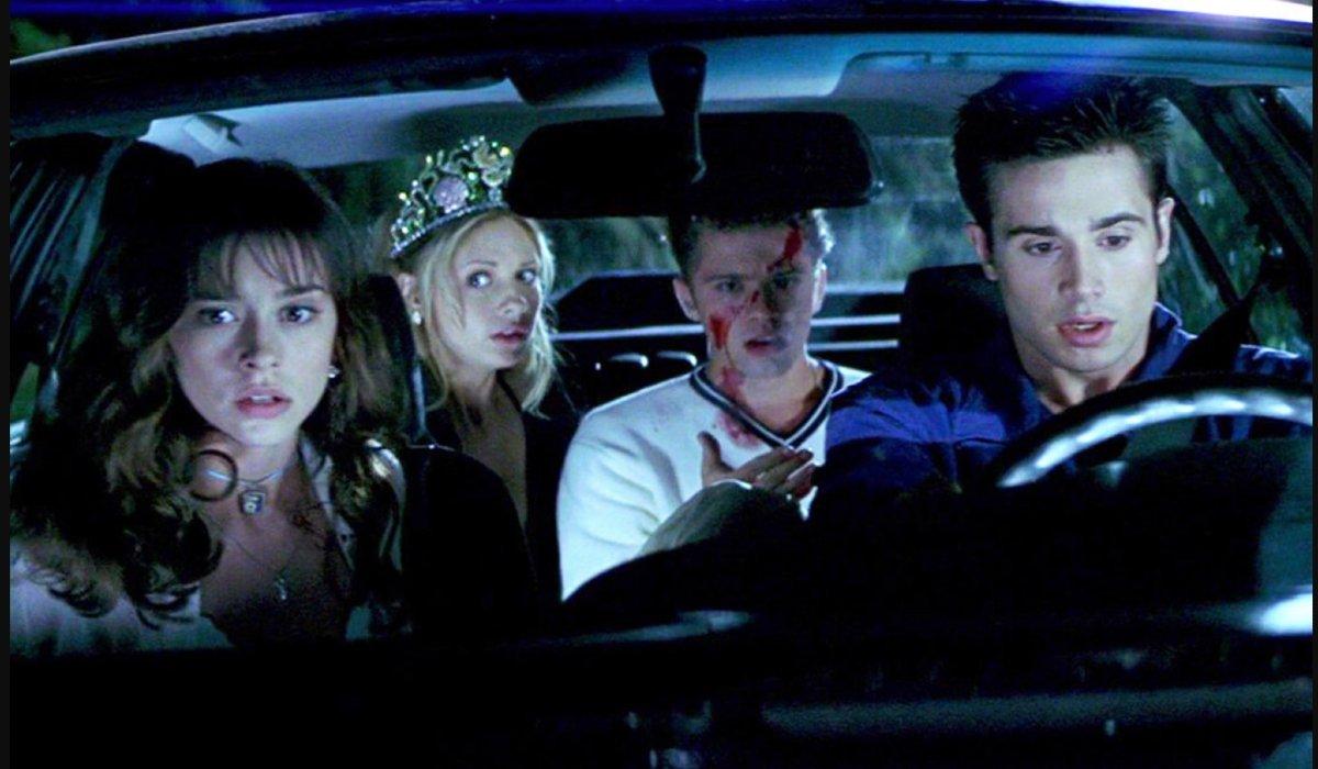 Jennifer Love Hewitt, Sarah Michelle Geller, Ryan Phillippe, and Freddie Prinze Jr. sitting in a car, shocked, in I Know What You Did Last Summer.