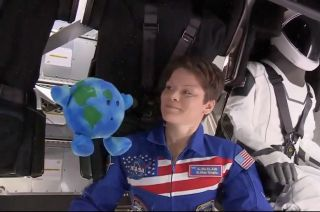 Expedition 58 flight engineer Anne McClain of NASA looks on as a Celestial Buddies' Planetary Pal Earth plush toy floats in zero-g on board SpaceX's first Crew Dragon spacecraft to dock to the International Space Station on Sunday, March 3, 2019.