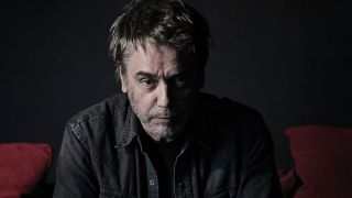 Jean Michel Jarre in shadows on a red sofa