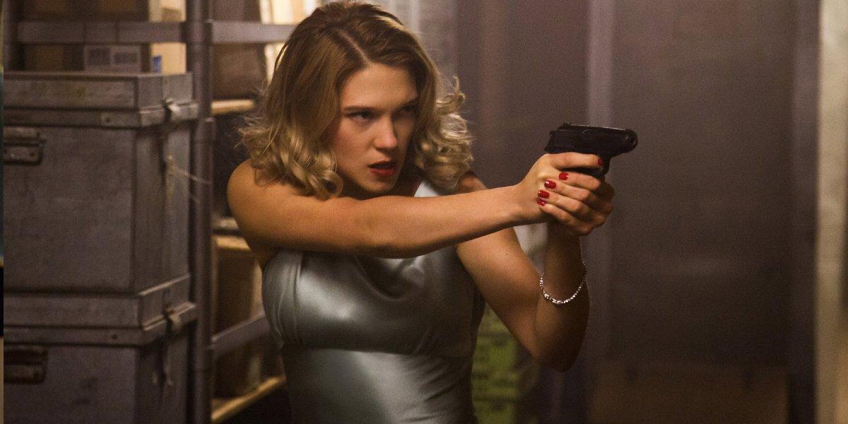 Léa Seydoux aims her gun in a train compartment in Spectre.