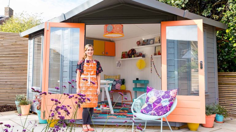 Colourful painted garden shed with open double doors and chair outside