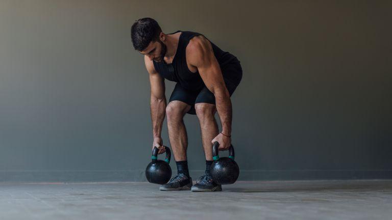 Man doing deadlifts with kettlebells
