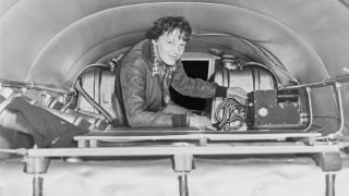 Amelia Earhart checking equipment on her airplane, circa 1937.