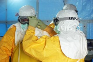 Health care workers put on protective gear before entering an Ebola treatment unit in Liberia during the 2014 Ebola outbreak..