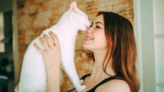 Why do cats lick you? White cat licking woman on the nose
