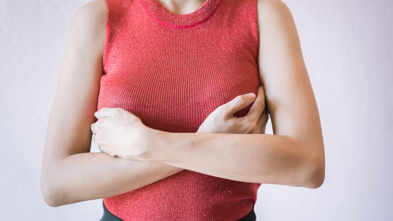 midsection of woman checking breasts wearing red jumper