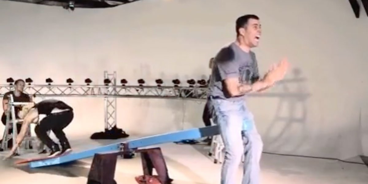 Steve-O dressed in blue jeans and a grey shirt getting hit in the nuts with a makeshift seesaw after someone jumped on the other end.