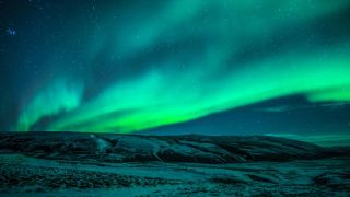 An aurora glows in skies over Iceland.